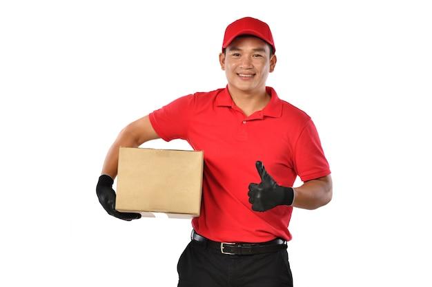 Азиатский доставщик в красной форме с картонной коробкой посылки, изолированной на белом