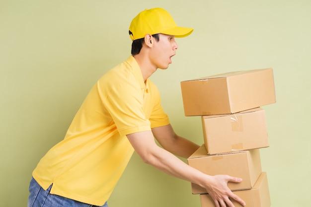 アジアの配達人は彼と一緒にカートンを持って、商品を配達するために走っています