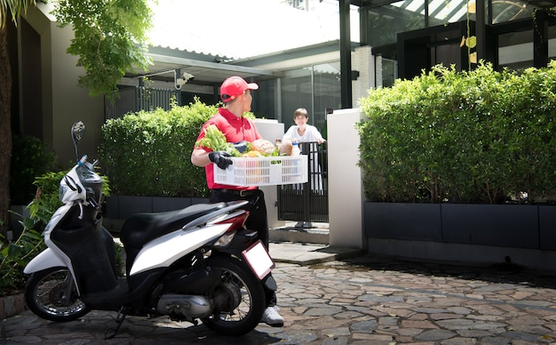 Asian delivery man in red uniform delivering  groceries box of food, fruit, vegetable and drink to woman recipient at home