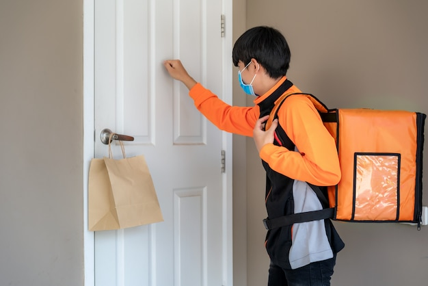 Asian delivery man send food bag at door knob for contactless or contact free from delivery rider in front house for social distancing for infection risk. coronavirus concept