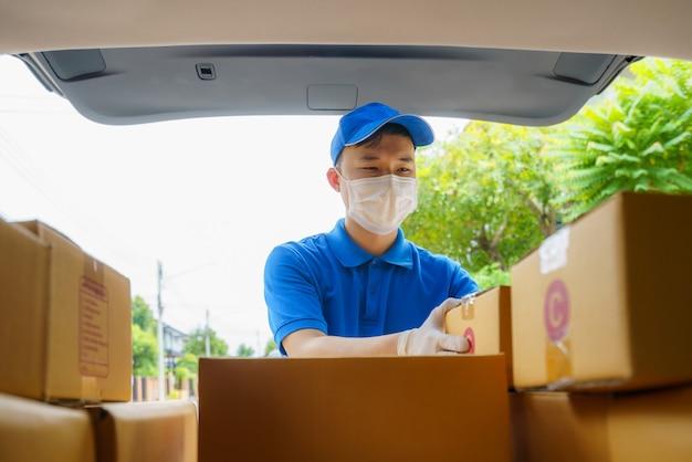 Asian delivery manは、コロナウイルス(covid-19)のパンデミック時にバンの段ボール箱を使用して宅配便業者にサービスを提供し、安全のために医療用マスクとラテックス手袋を着用します。
