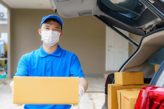 아시아 인 배달원은 코로나 바이러스 (covid-19) 대유행 기간 동안 밴에있는 판지 상자를 가지고 일하는 택배, 안전을 위해 의료 마스크와 라텍스 장갑을 착용 한 택배를 서비스합니다.