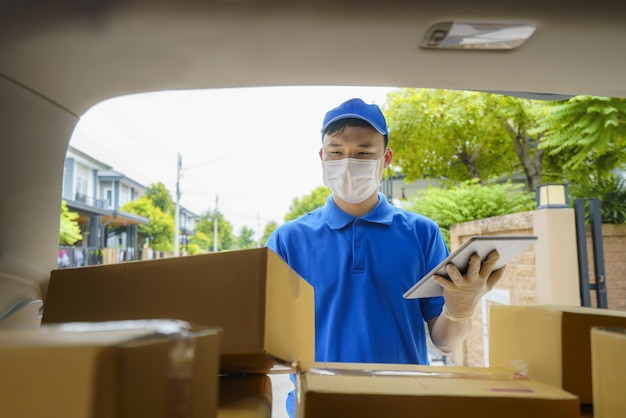 Asian delivery man services courier working with cardboard boxes on van