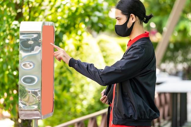 キオスクを使用して食品を注文し、このインライン注文をファストフードレストランの顧客に受け取るアジアの配達人オンライン技術のセルフサービスの新しい通常のレストランのコンセプト。