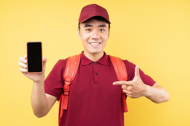 黄色の壁にポーズをとって赤い制服を着たアジアの配達人
