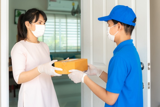 Азиатский курьер, носящий маску и перчатку в синей форме с картонными коробками в передней части дома и женщина, принимающая доставку коробок от доставщика во время вспышки covid-19.