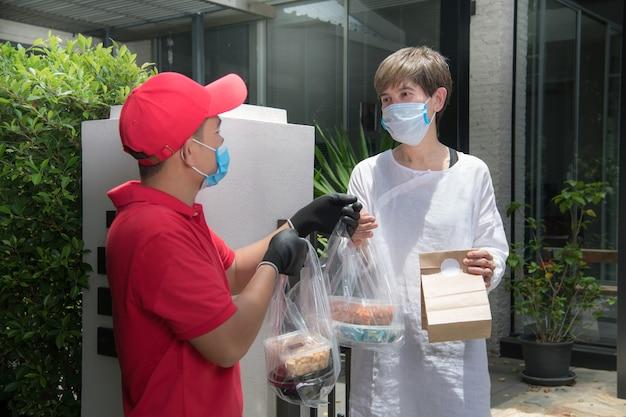 Азиатский курьер в маске и перчатках в красной форме доставляет пакет с едой и напитками получателю во время вспышки covid-19