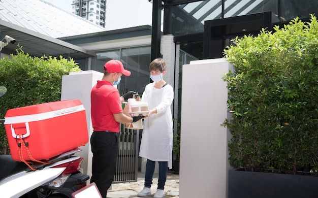 음식과 음료의 가방을 제공하는 빨간 제복을 입은 얼굴 마스크와 장갑을 끼고 아시아 배달 남자