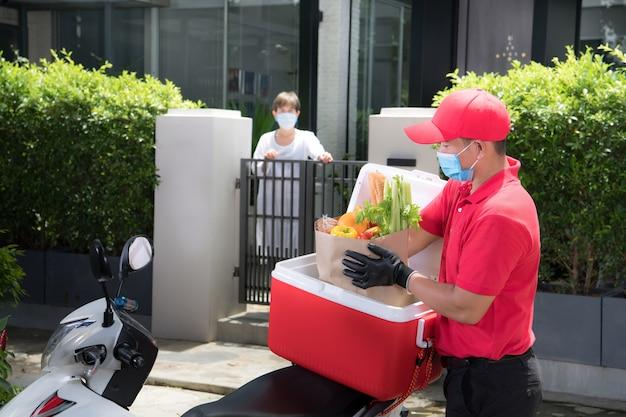Азиатский курьер в маске и перчатках в красной форме доставляет сумку с продуктами