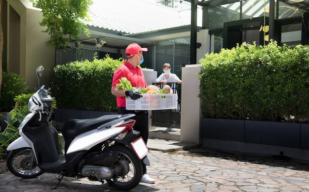 Азиатский курьер в маске и перчатках в красной форме доставляет коробку с продуктами