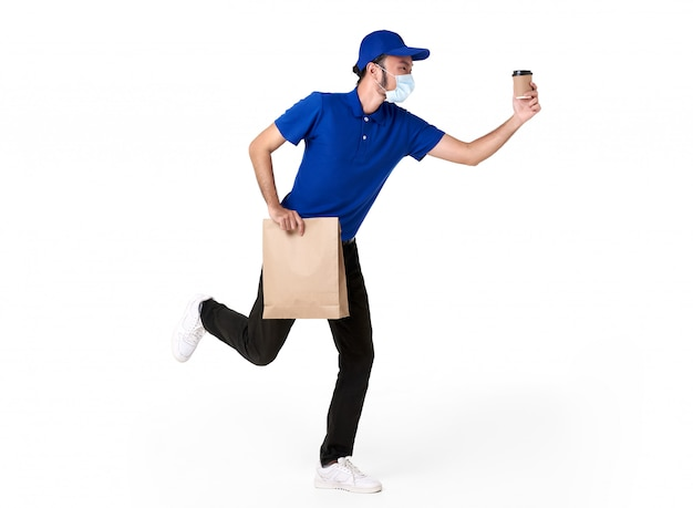 Asian delivery man wearing face mask in blue uniform running with paper bag and takeaway coffee isolated over white space. express delivery service during covid19.