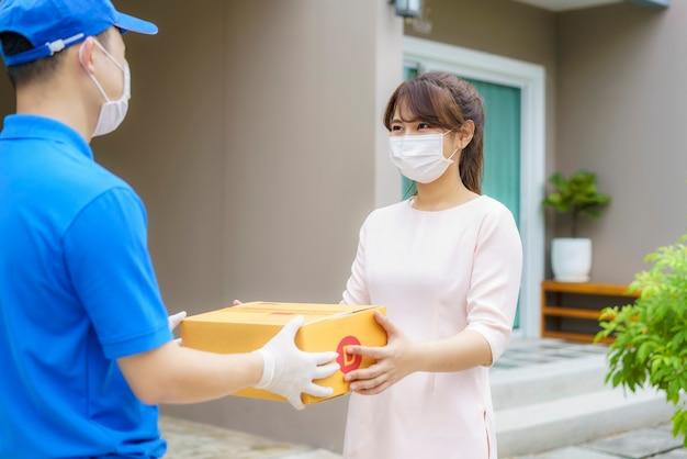 골 판지 상자를 들고 얼굴 마스크를 쓰고 아시아 배달 남자