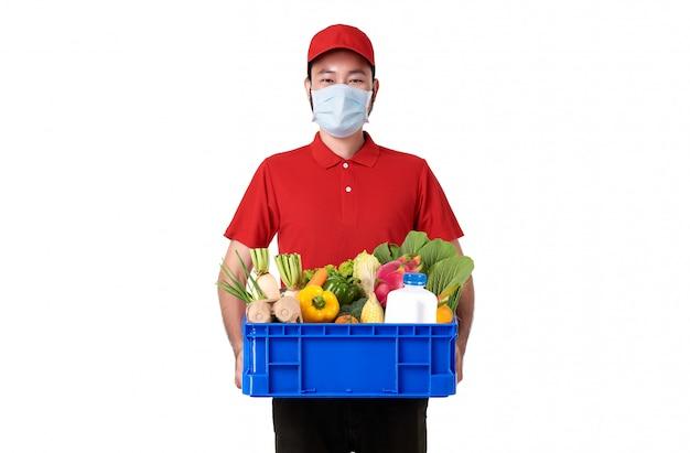 白い背景で隔離された生鮮食品のバスケットを保持している赤い制服を着たフェイスマスクを着ているアジアの配達人。 covid19中の速達サービス。