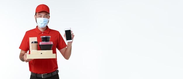 Азиатский доставщик в маске в красной форме держит ланч-бокс и кофе на вынос и показывает приложение для мобильного телефона, изолированное на белом фоне. служба экспресс-доставки во время covid19.