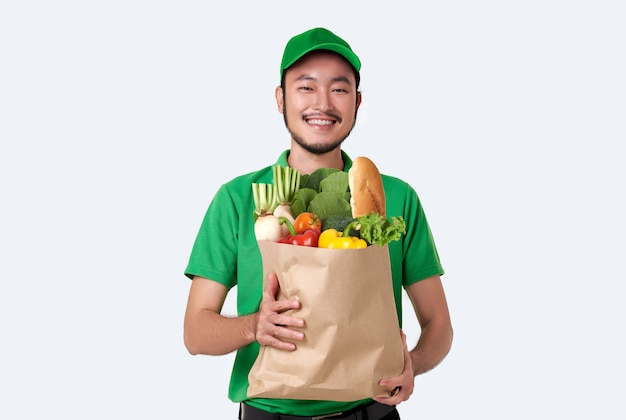 Asian delivery man wearing in green uniform holding fresh food paper bag isolated over white space.