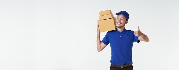 白い背景の上に分離されたキャリー小包郵便ポストと青い制服を着て立っているアジアの配達人。速達サービス。パノラマの背景。
