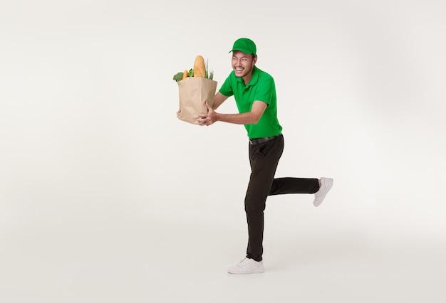 Азиатский доставщик в зеленой форме, держащий бумажный пакет свежих продуктов и работающий на белом фоне. концепция экспресс-доставки.