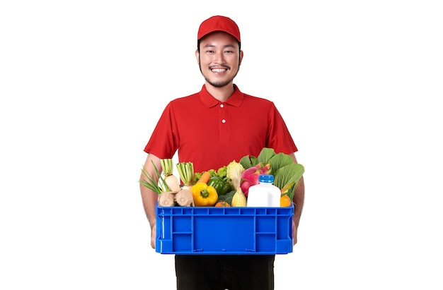 Азиатский доставщик в красной форме, держащий корзину со свежими продуктами, изолированную над белой стеной.