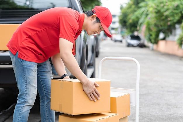 赤い制服と赤い帽子を身に着けているアジアの配達人が小包ボックスを移動して転送します。