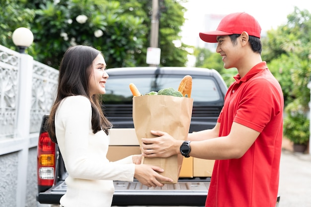Asian delivery man wearing red uniform, red hat holding paper bag