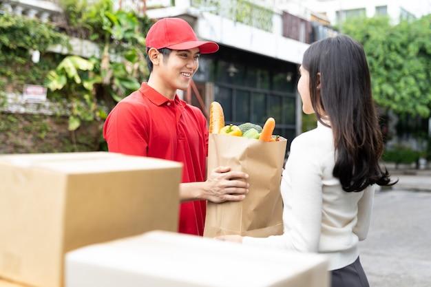 Азиатский курьер в красной форме, красная шляпа держит бумажный пакет