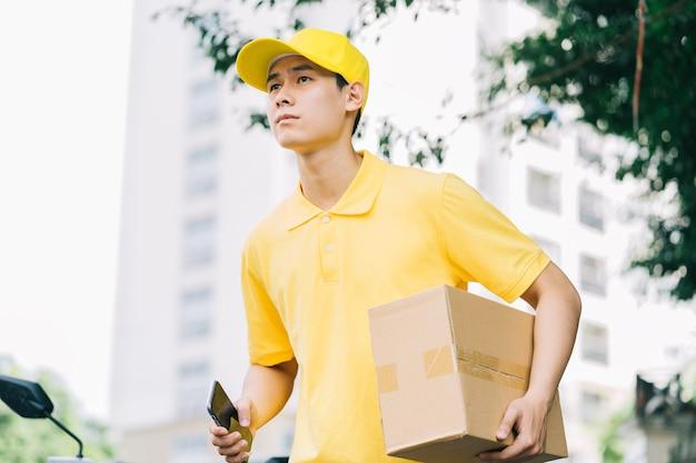 アジアの配達員が顧客に商品を配達するために道路を走っています