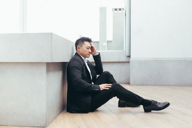 사무실 비즈니스 센터 건물 근처 야외 거리에 앉아 있는 아시아 우울한 남자
