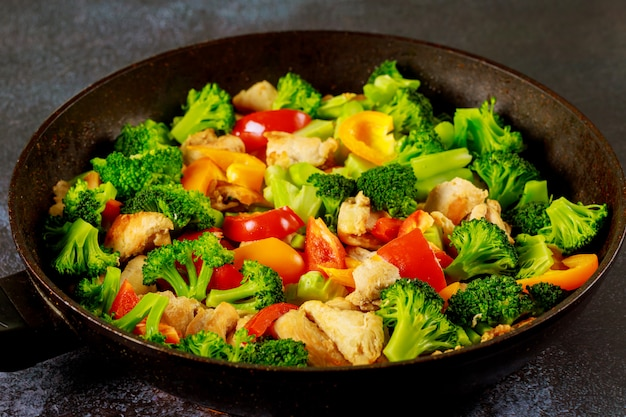 Asian dish chicken with paprika and broccoli in wok