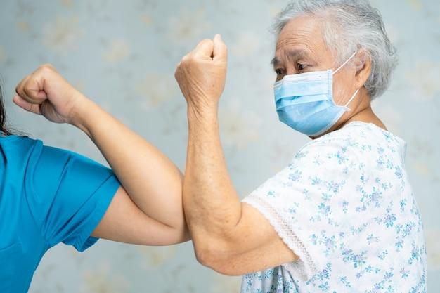Азиатский врач и пожилой пациент трясутся локтями, чтобы дистанцироваться от общества, чтобы избежать коронавируса covid-19.