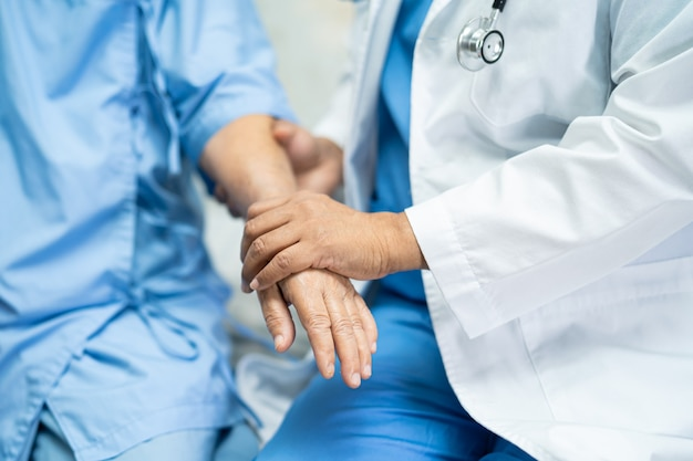 Asian doctor care, help and support senior woman patient at hospital.