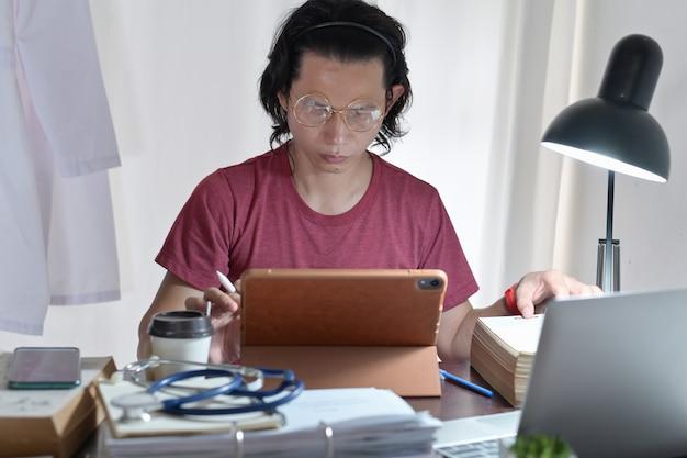 医療オンライン知識を読んで研究しているアジアの医師のカジュアルウェア