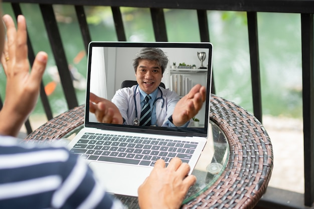 Азиатский врач помогает снять стресс и дает пациентам знания и понимание о офисном синдроме через интернет.