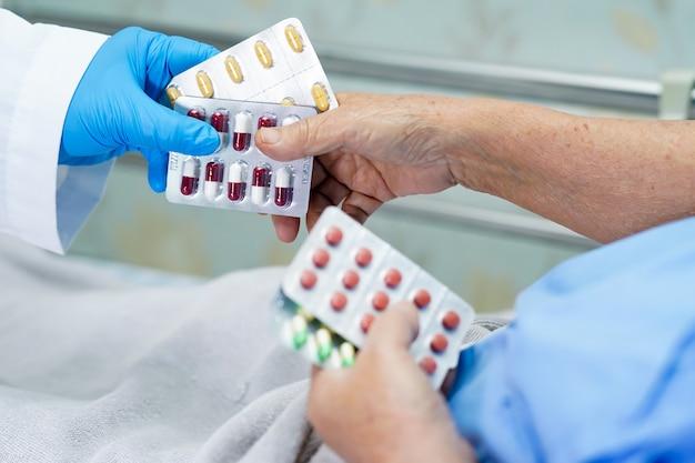 Азиатский доктор держа пилюльки капсулы антибиотиков в упаковке волдыря с старшим пациентом.