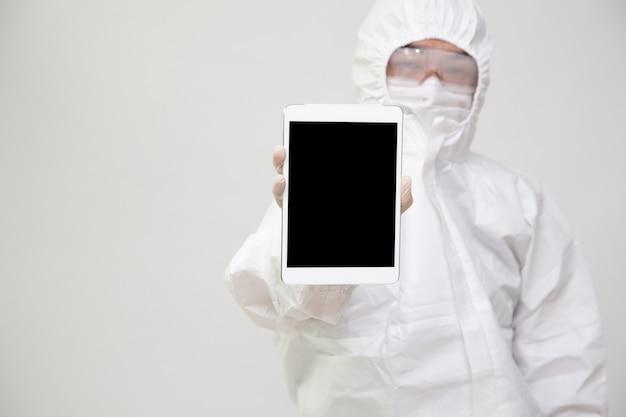 分離されたタブレットを保持しているアジアの医師