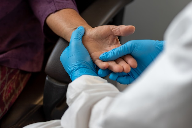Asian doctor is checking patience's pulse by fingers, medical checking on table. the aging female patient that is at risk for infection corona virus [covid-19].