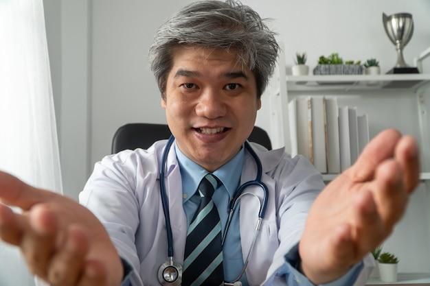 아시아 의사는 인터넷 응용 프로그램에서 환자와 온라인으로 방문하고 증상을 기록합니다.