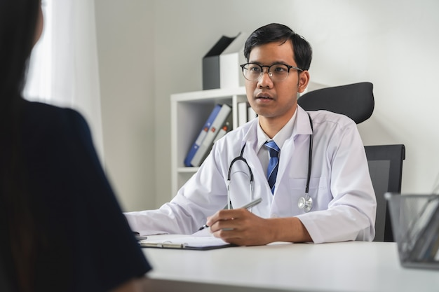 Asian doctor is report the symptoms and advising the patient.