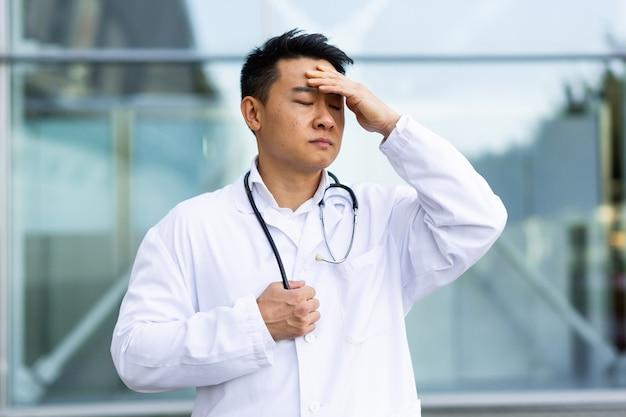 Азиатский врач устал после работы, подавлен и разочарован работой, проделанной на улице возле клиники