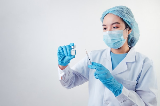 Asian doctor looking and preparing syringe vaccine and vial for injection to illness patient on white background. medical people and illness prevention technology concept. coronavirus epidemic theme