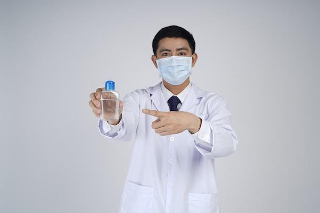 手指消毒剤と医療マスクのアジアの医者の男
