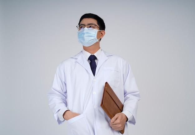 Азиатский доктор мужчина в белом халате, медицинская маска смотрит вверх с позитивным взглядом