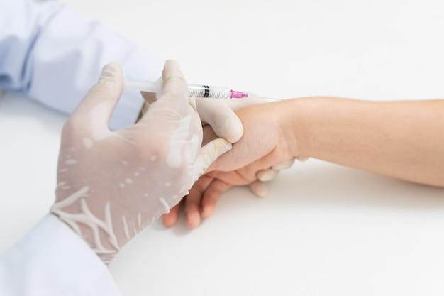 Азиатские руки доктора или медсестры при шприц впрыскивая для запястья руки медицинский. проблемы с костью запястья болезненные запястья, вызванные длительной работой. кистевой туннельный синдром, артрит, неврологические заболевания