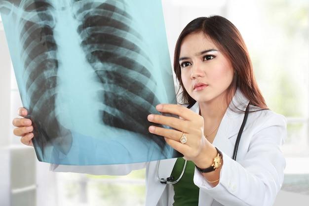 X線を見る白いコートと聴診器を着ているアジアの医師