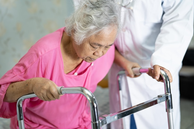 Asian doctor support senior woman patient walk with walker at hospital.