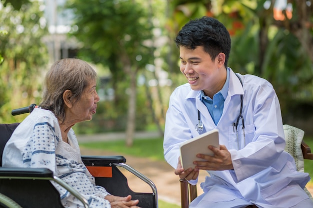 Asian doctor talking with elderly female patient on wheelchair