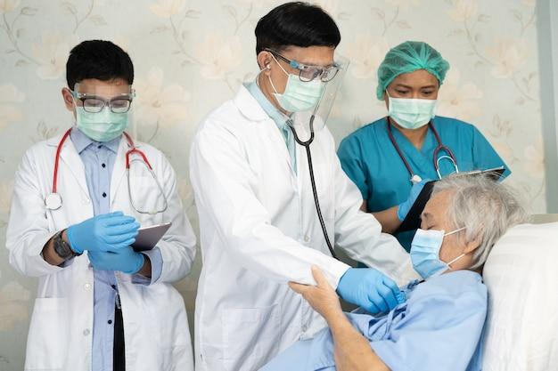 アジアの医師チームは、病棟で感染症covid-19コロナウイルスを治療するための新しい正常な動機付けの病気について老婦人患者をチェックします。
