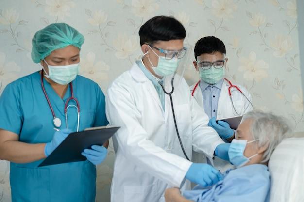 Азиатская команда врачей проверяет пациента пожилого возраста на лечение инфекции коронавируса covid19