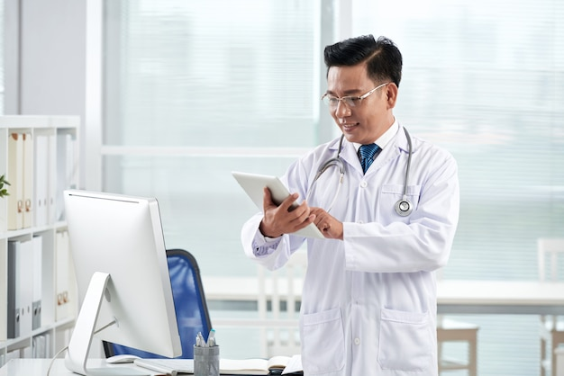 Азиатский доктор с помощью медицинского приложения на своем цифровом устройстве