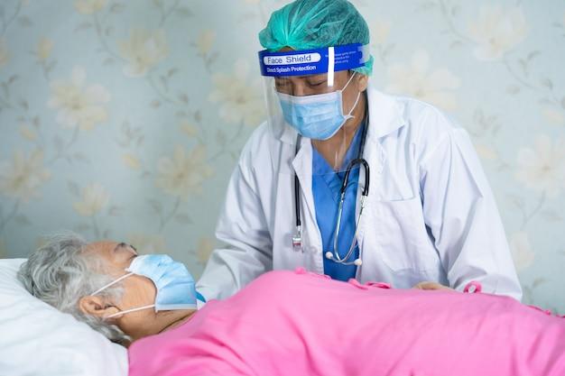 Азиатский врач в защитной маске и новом костюме сиз для проверки защиты пациента от инфекции, вызванной вспышкой коронавируса covid-19, в карантинной больничной палате.