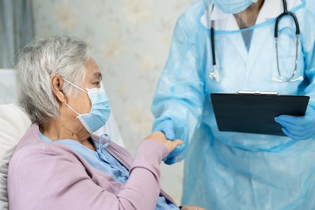 フェイスシールドとppeを身に着けているアジアの医師は、患者が安全感染を保護することを確認するために新しい通常のスーツを着用します。検疫看護病院病棟でのcovid19コロナウイルスの発生。